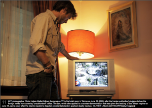 "AFP photographer Olivier Laban-Mattei follows the news on TV in his hotel room in Tehran on June 16, 2009, after being banned from covering ""unauthorized"" rallies. Photo by OLIVIER LABAN-MATTEI/AFP/Getty Images."